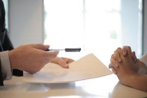 A person handing over a pen to another person to sign the contract after buying a second home in Florida.
